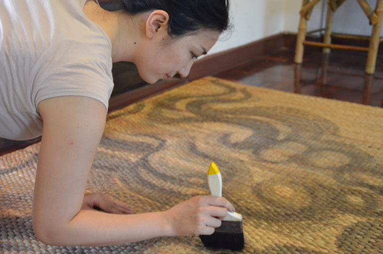 Fumie Mune at work, hand-painting a Zen Kodo mat.